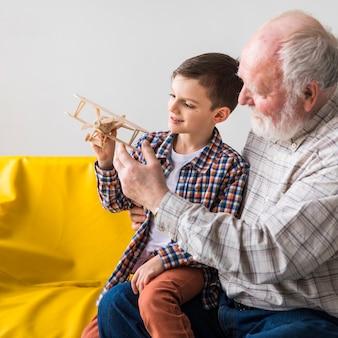 Großvater und enkel, die spielzeugflugzeug spielen