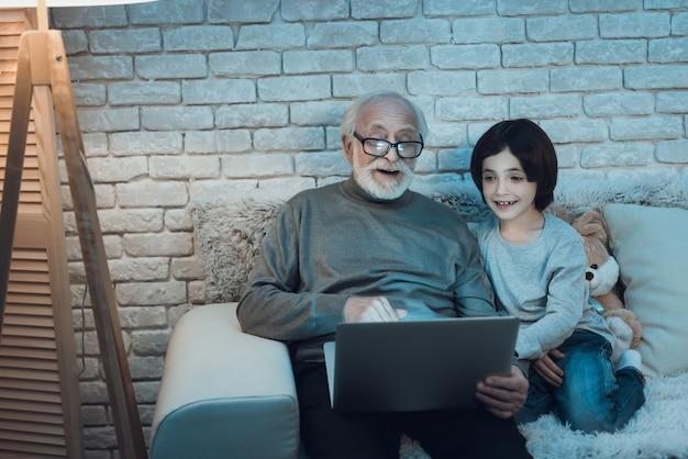 Großvater und enkel, die zusammen laptop verwenden