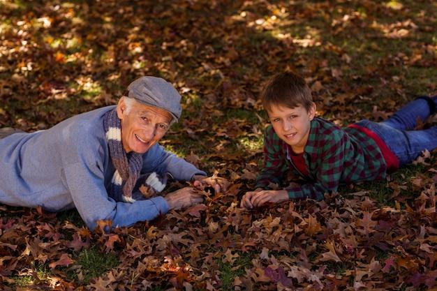 Großvater und enkel liegen auf herbstlaub