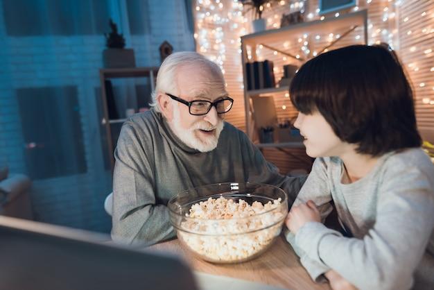 Großvater und enkel schauen film auf laptop