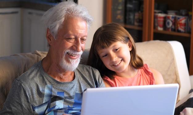 Großvater und enkel unterhalten sich und grüßen, indem sie einen videoanruf an den pc tätigen