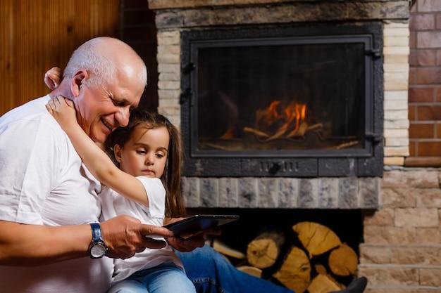 Großvater und enkelin, die tablette eines hauses nahe dem kamin verwenden