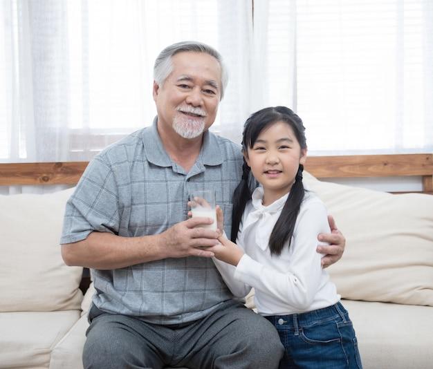 Großvater und enkelin sitzen auf einem sofa