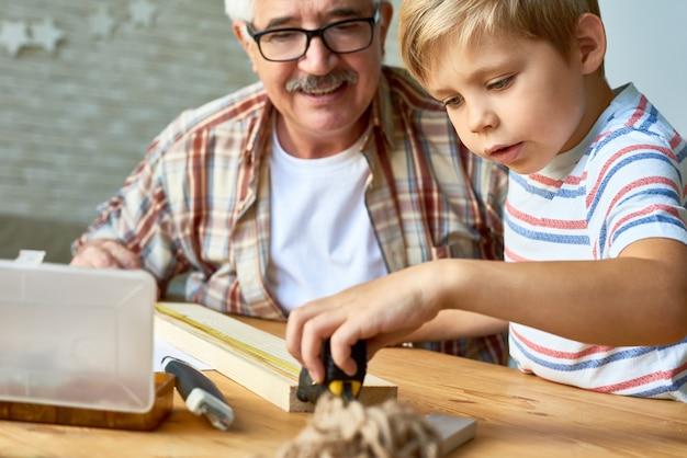 Großvater und kleiner junge arbeiten mit holz