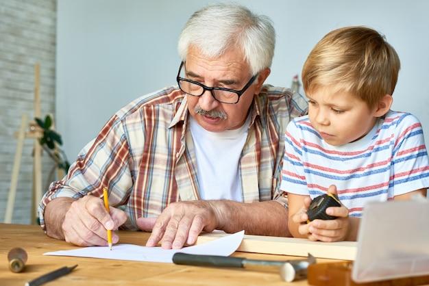 Großvater und kleiner junge arbeiten zusammen