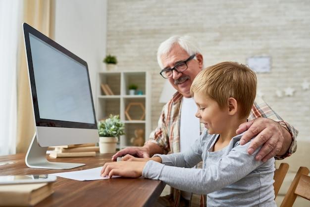 Großvater und kleiner junge mit computer