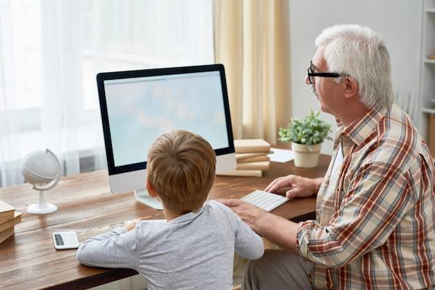 Großvater und kleiner junge mit pc