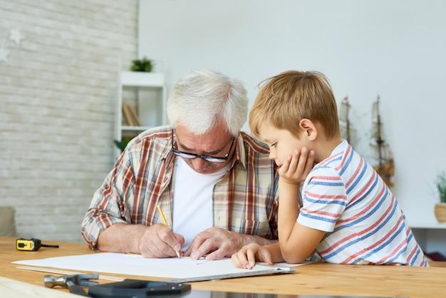 Großvater und kleiner junge zeichnen zusammen