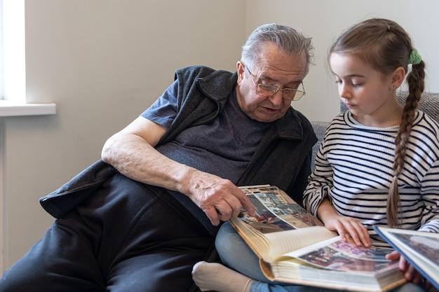 Großvater und seine kleine enkelin schauen sich bilder im familienfotoalbum an.