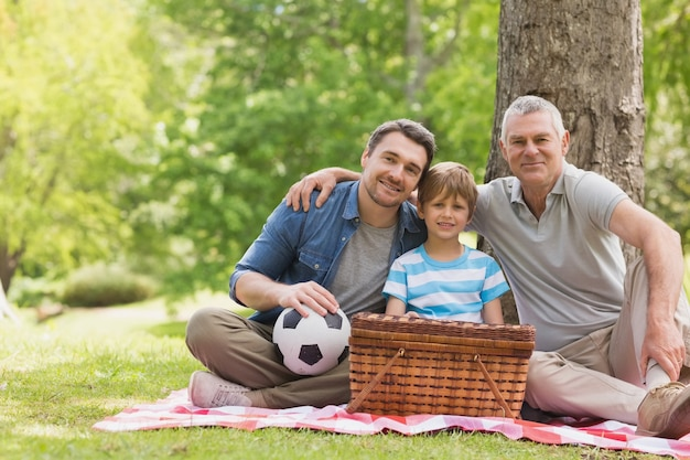 Großvater, vater und sohn mit picknickkorb am park