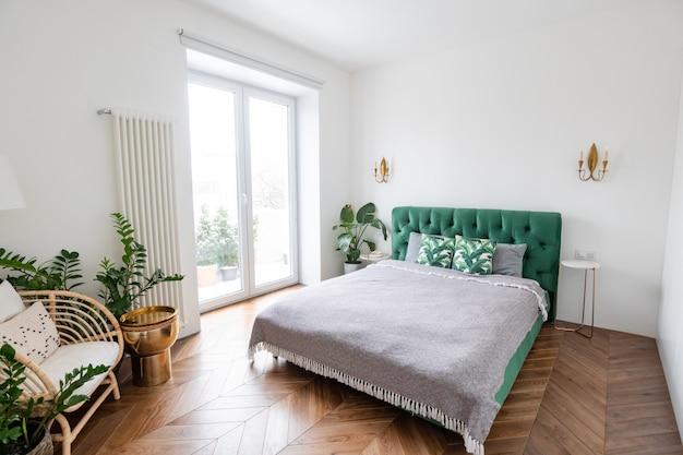 Großzügiges schlafzimmer mit doppelbett, großen schiebefenstern und hohen decken