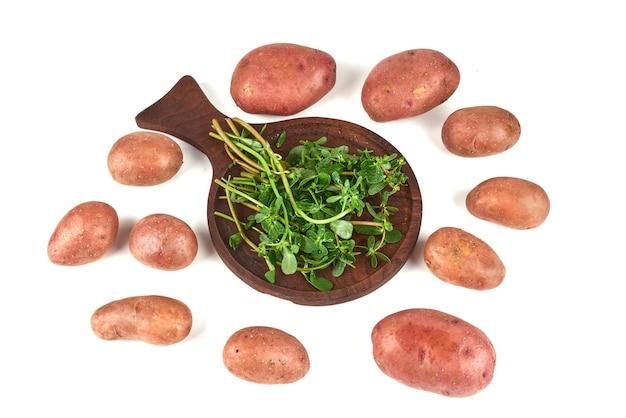 Grün auf einer holzplatte mit kartoffeln.