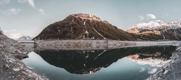 Grün bedeckter berg, der auf ruhigem wasser unter klarer himmelslandschaft reflektiert wird