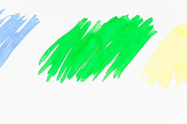 Grün; blauer und gelber pinselstrich auf weißem hintergrund