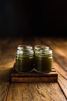 Grün gefärbte alkoholische schützen oder schussgetränke auf holztisch kopieren platz