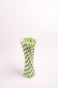 Grün und weiß gestreifte trinkröhrchen in einem glas, das auf einem hellen hintergrund lokalisiert wird