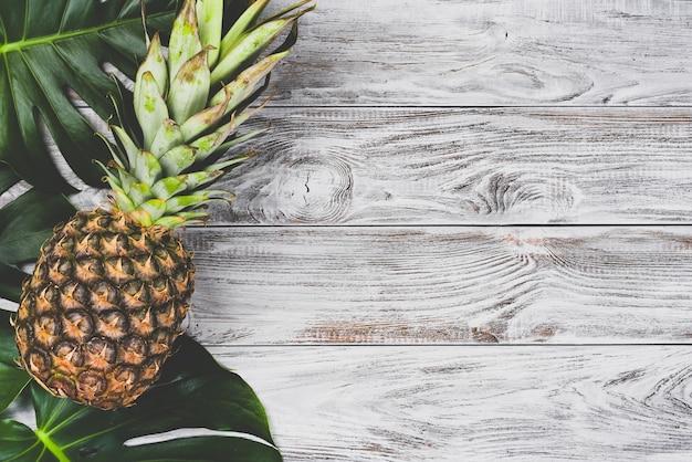 Grün verlässt monstera mit einer rohen ananas auf weißer hölzerner tischoberansicht.