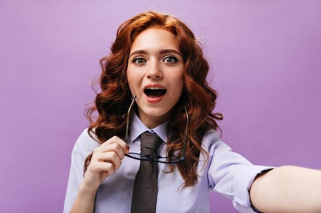 Grünäugige dame hält eine brille und macht ein selfie an einer lila wand