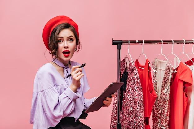 Grünäugige dame im roten hut und mit den roten lippen hält tablette und betrachtet kamera vor dem hintergrund von kleiderbügeln mit kleidern.