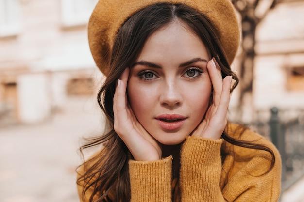 Grünäugiges mädchen in der orangefarbenen baskenmütze schaut in die kamera. brünette frau im wollpullover, der draußen aufwirft. schnappschuss der schönen kaukasischen dame