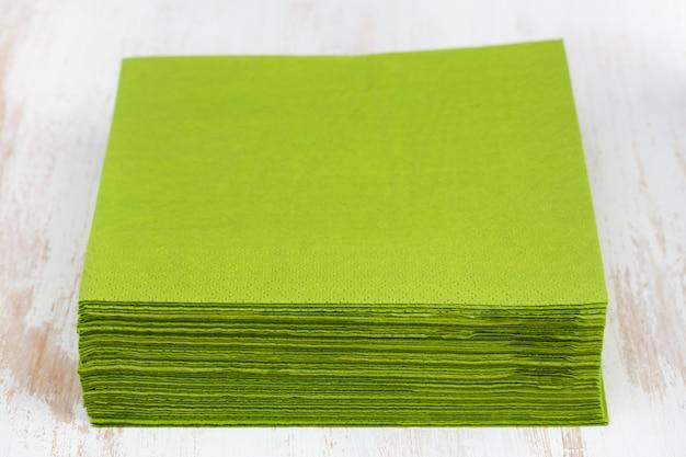 Grünbuchserviette auf weißer holzoberfläche