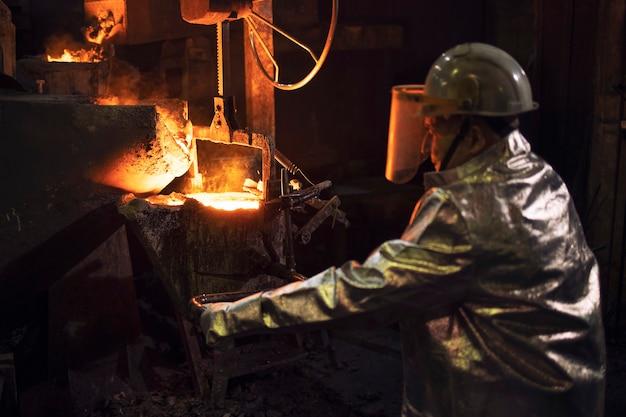 Gründer im schutzanzug arbeitet mit heißem flüssigem stahl in der gießerei.