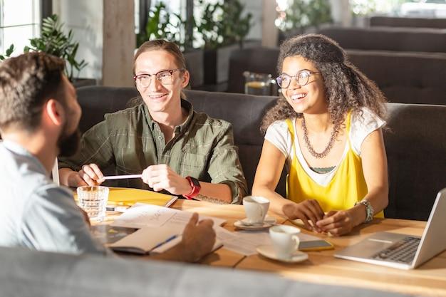 Gründung eines neuen geschäfts. positive fröhliche freunde, die gute laune haben, während sie über ihre startup-ideen diskutieren