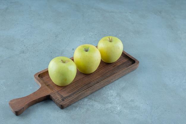 Grüne äpfel auf einem brett, auf dem marmorhintergrund. foto in hoher qualität