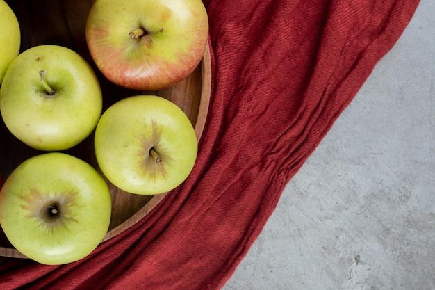 Grüne äpfel auf einem tablett auf marmoroberfläche