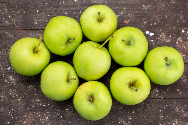 Grüne äpfel der draufsicht auf dem braunen hölzernen schreibtisch frischer apfelfrucht milder