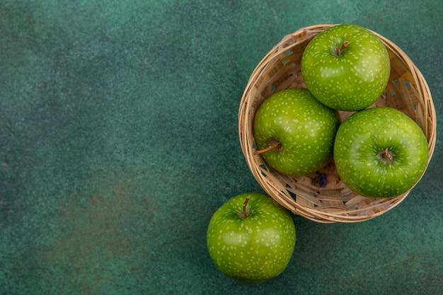 Grüne äpfel der draufsicht kopieren raum in einem korb auf einem grünen hintergrund