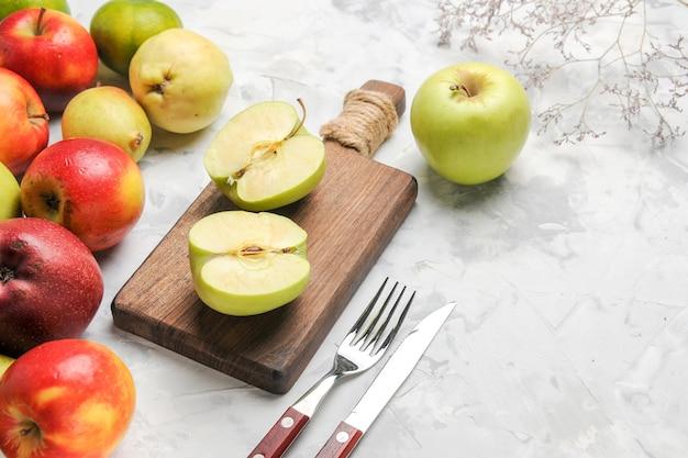Grüne äpfel der vorderansicht mit anderen früchten auf der reifen birne der weißen tischapfelfrucht frisch