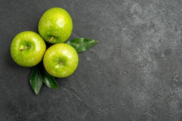 Grüne äpfel drei grüne äpfel mit blättern auf dem dunklen tisch