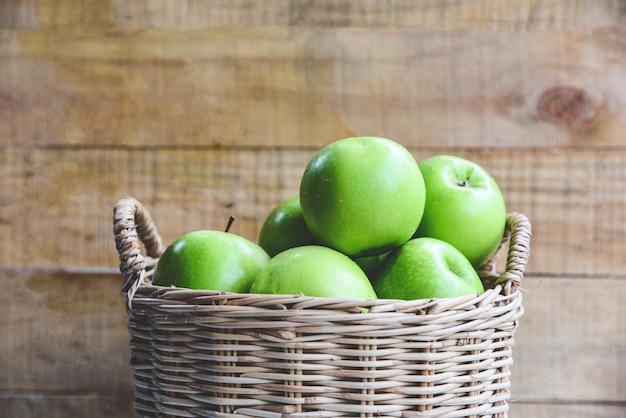 Grüne äpfel - ernten sie apfel im korb auf holz