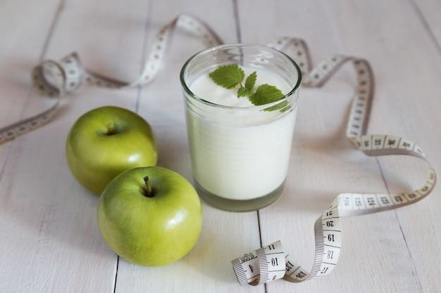 Grüne äpfel, glas joghurt und maßband