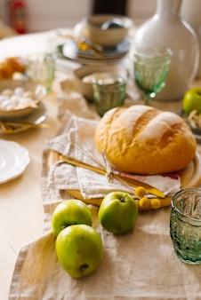 Grüne äpfel, hausgemachtes frisches weizenbrot. frühstück zu hause servieren