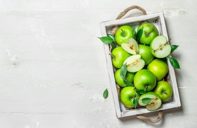Grüne äpfel in einem holztablett.
