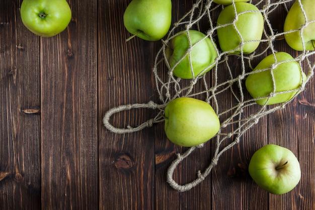 Grüne äpfel in einem netzbeutel und herum auf einem hölzernen hintergrund. draufsicht. platz für text
