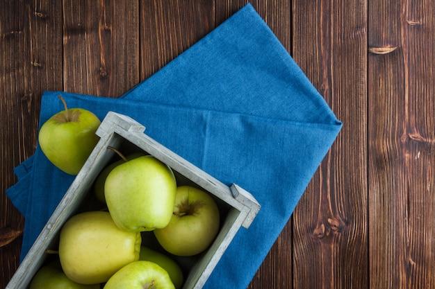 Grüne äpfel in einer holzkiste auf einem blauen stoff und einem hölzernen hintergrund. flach liegen.