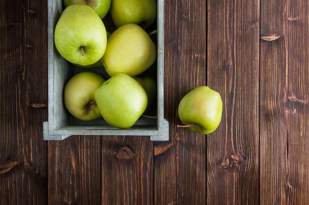 Grüne äpfel in einer holzkiste auf einem hölzernen hintergrund. flach liegen. freier speicherplatz für ihren text