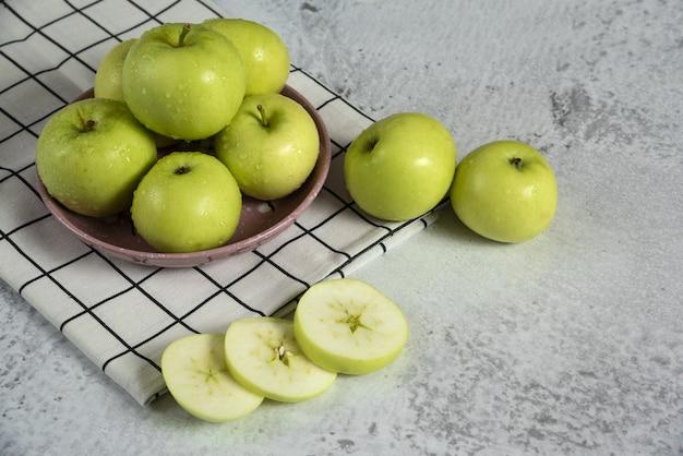 Grüne äpfel in einer keramik-untertasse auf dem handtuch, draufsicht