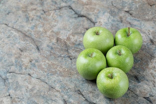 Grüne äpfel isoliert auf grauem marmor.