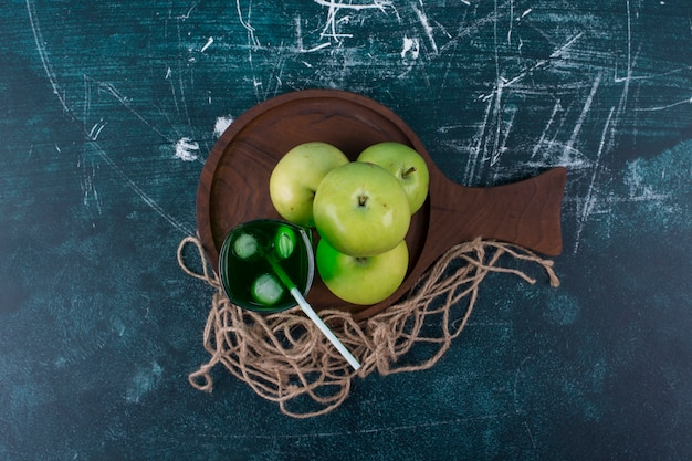 Grüne äpfel mit einem glas saft auf einem rustikalen hintergrund in der mitte.