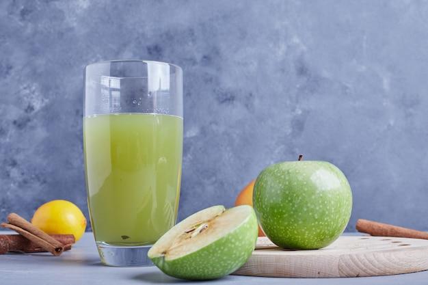 Grüne äpfel mit einem glas saft.