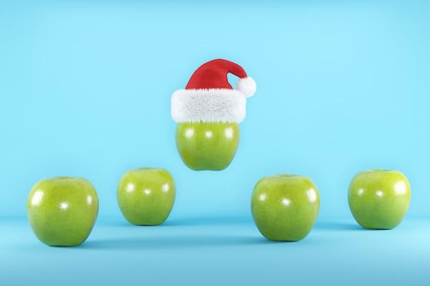Grüne äpfel mit santa hat, die auf blau schwimmt