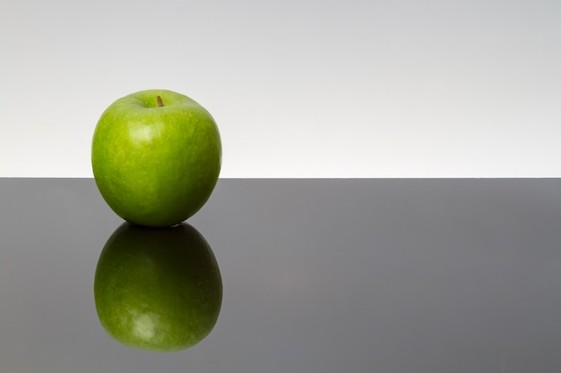 Grüne äpfel mit wassertropfen auf reflektierendem tisch, isoliert auf dunklem hintergrund. kopierraum. spiegeloberfläche.