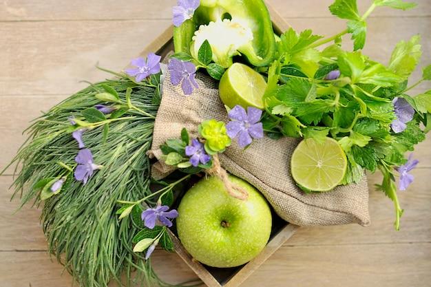 Grüne äpfel und limette, frühlingszwiebeln. herbst bouquet von früchten und blumen.