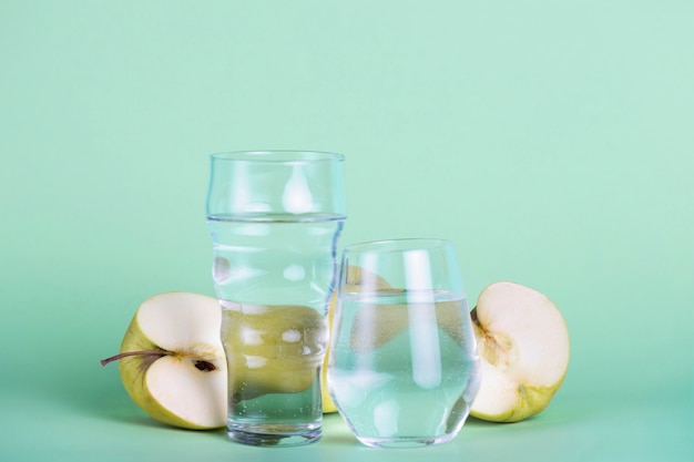 Grüne äpfel und unterschiedlich große gläser anordnung