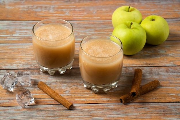 Grüne äpfel, zimtstangen und zwei tassen frischen saft auf dem tisch, draufsicht