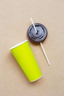 Grüne aper kaffeetasse mit stroh und plastikkappe auf furnierholz